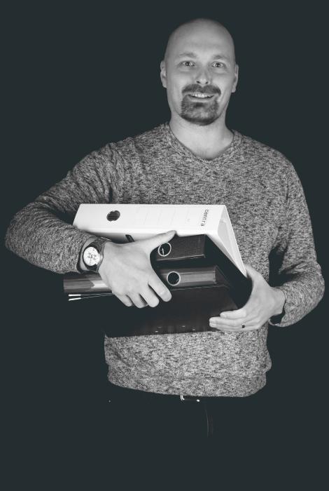Kirjanpitäjä Sami Rautiainen pitelee sylissään kasaa mappeja.