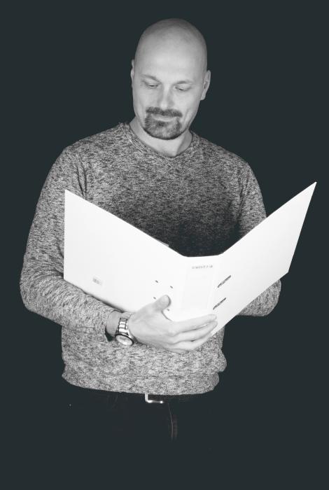Kirjanpitäjä Sami Rautiainen pitelee käsissään avointa mappia.
