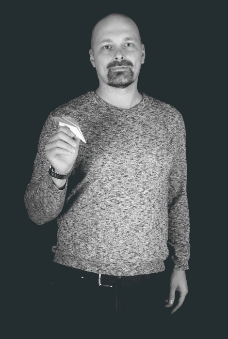Kirjanpitäjä Sami Rautiainen pitelee kädessään paperilennokkia.
